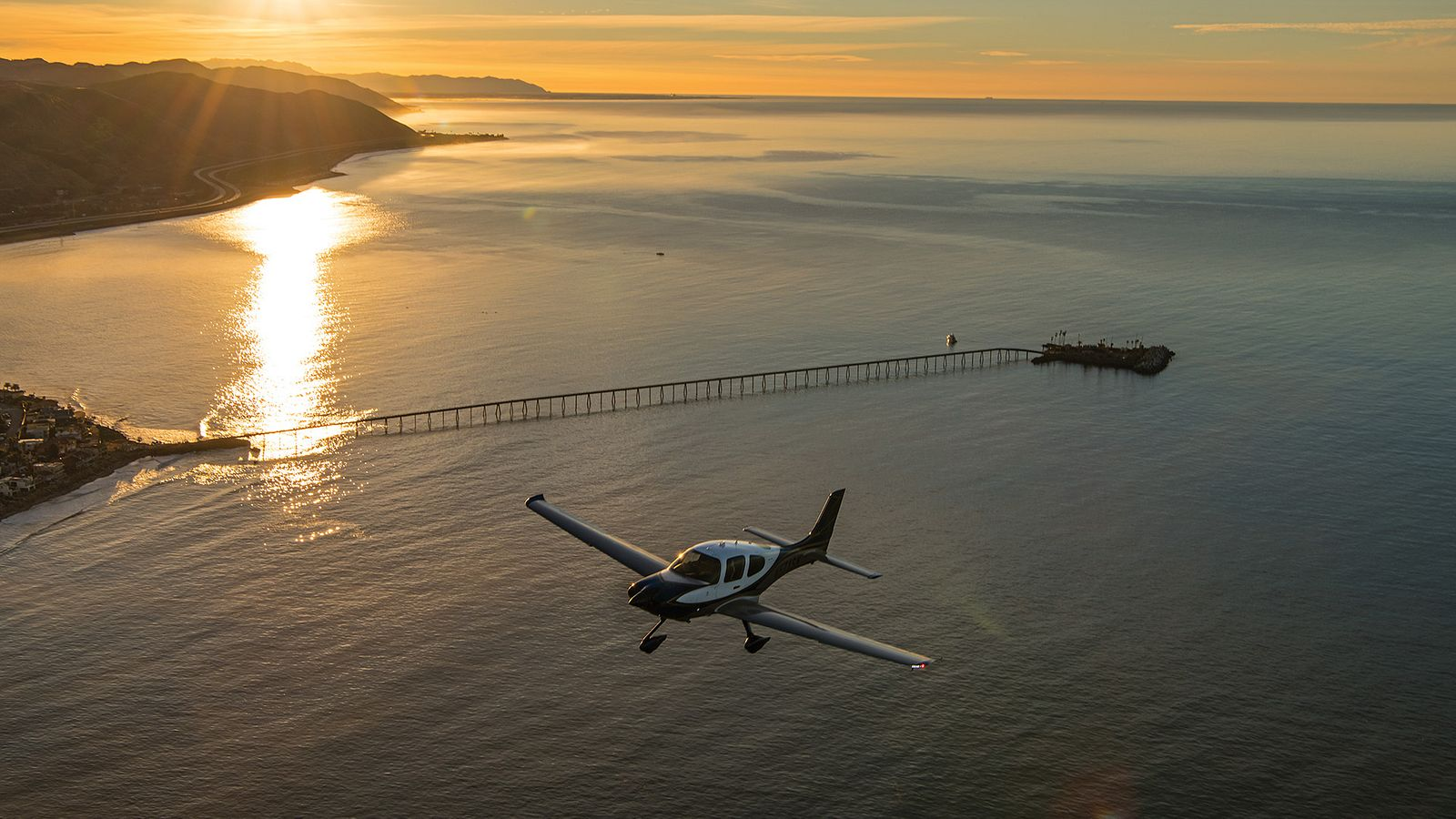 A Cirrus SR-22 is pictured flying mid-air against a Southern California Beach sunset, with a nearby boardwalk.
