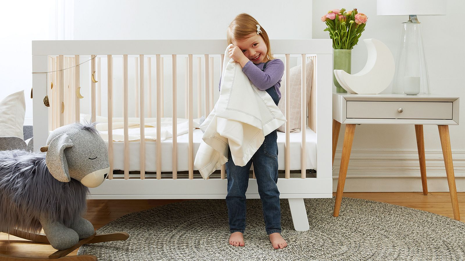 Toddler in her nursery, outside her crib, smiling as she is holding her beloved Ocochi blanket.