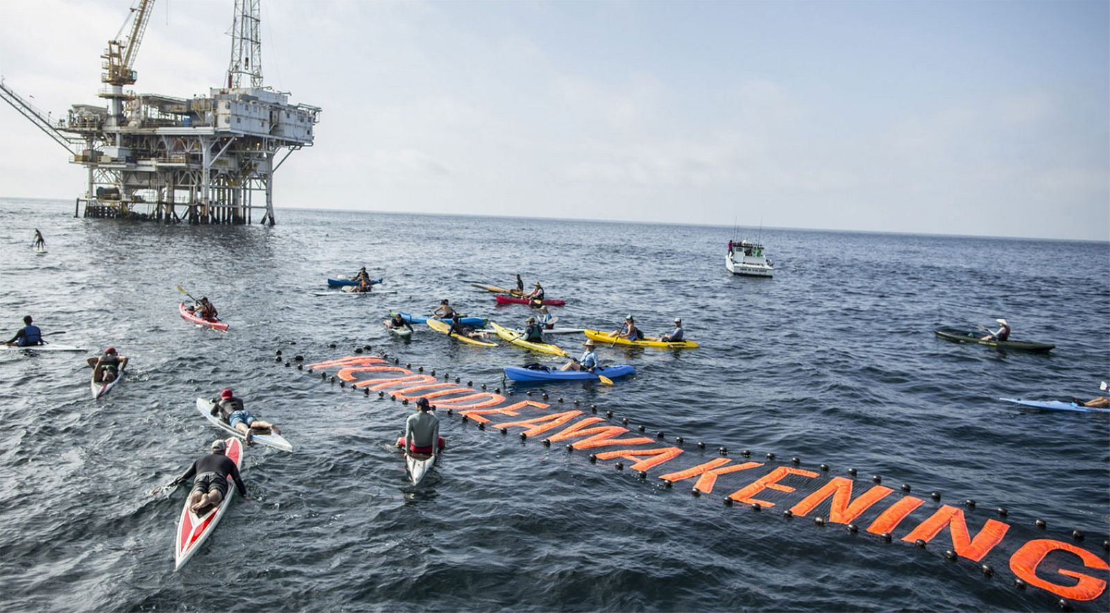 A floating banner reading '#CrudeAwakening' floats on the ocean, an oil rig in the background, with kayakers surrounding the banner.